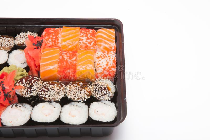 Big sushi set ib black plastic box on white background, top view close up, copy space royalty free stock images