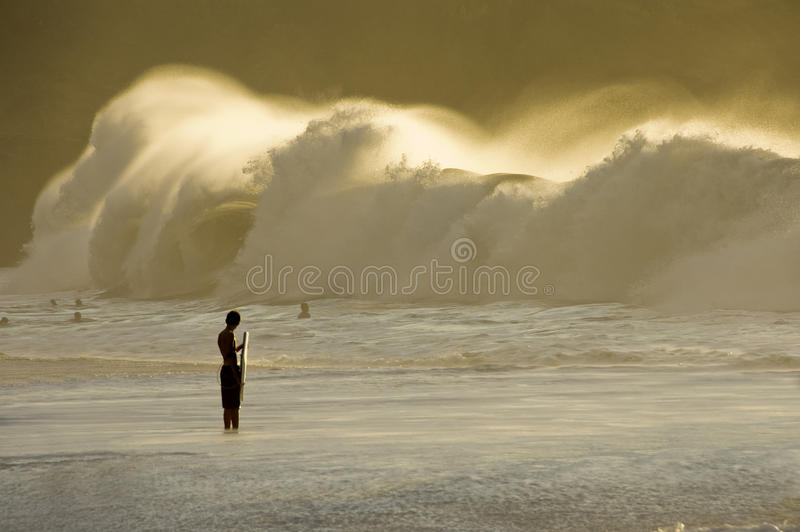 Big Swell. Big wave breaking on the shore and the silhouette of one bodyboarder watching it in the evening. Waimea Bay in the North Shore of Oahu. Hawaii royalty free stock image