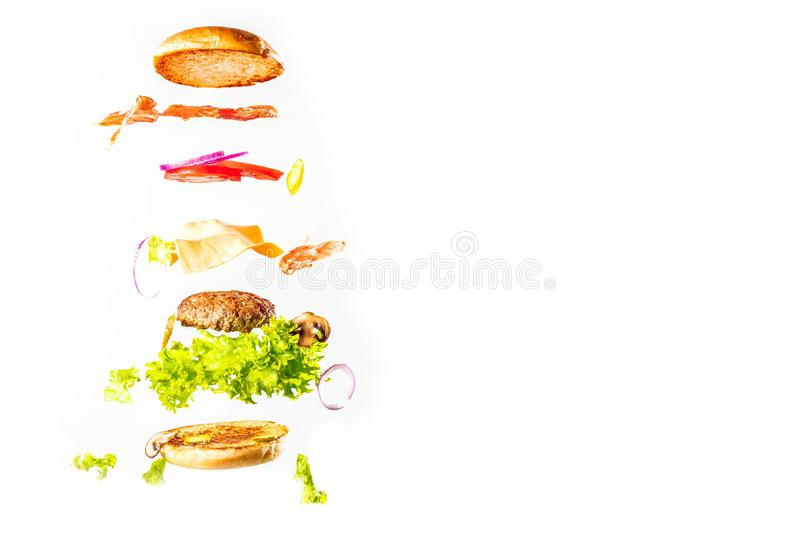 Big tasty home made burger with flying ingredients stock image