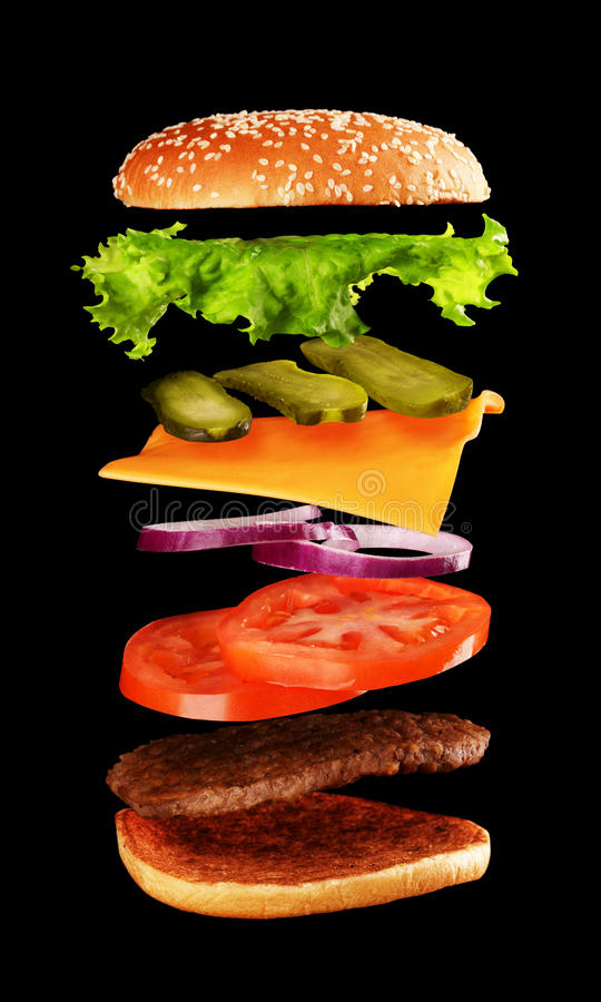 Big tasty home made burger with flying ingredients stock photography