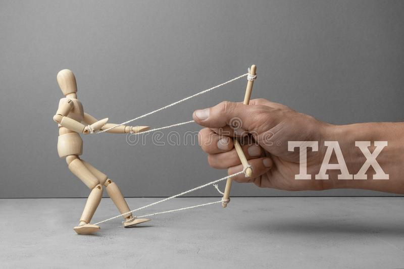 Big tax restrains business development as a puppeteer doll. The hand of the puppeteer is holding a scared wooden doll royalty free stock images