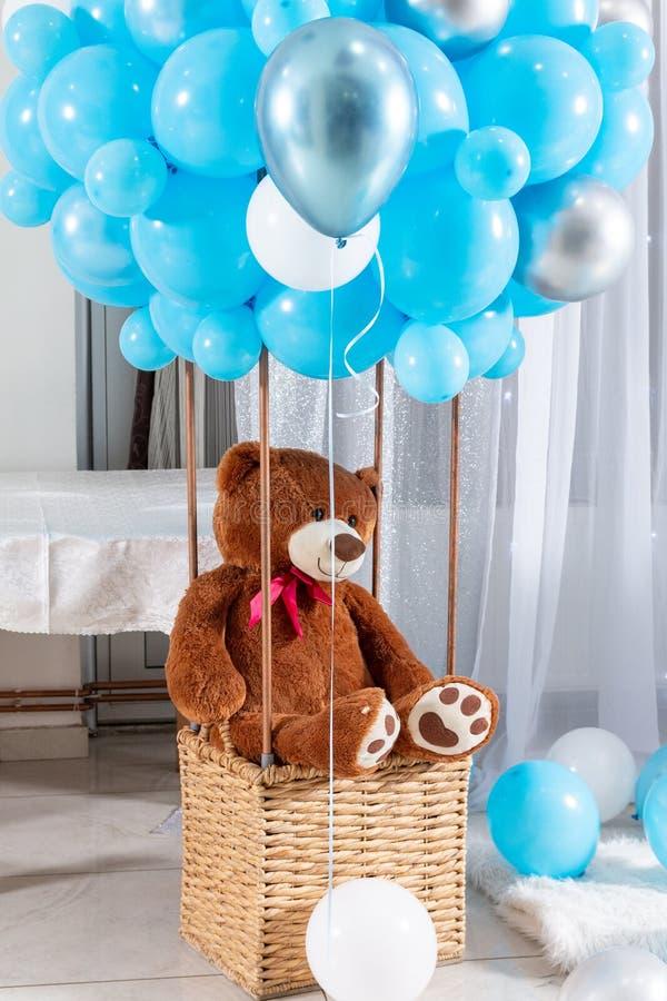 Big Teddy Bär im Ballonkorb mit blauen Ballons stockfotos