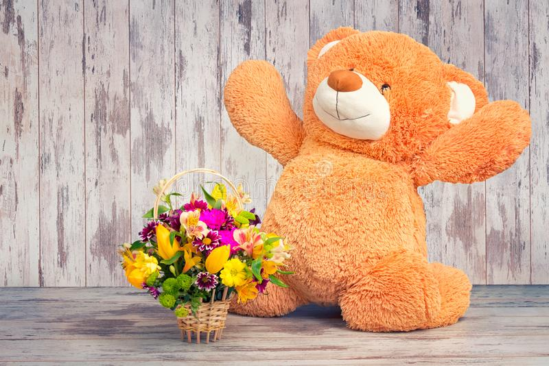 Big Teddy bear with a basket of spring flowers. Big Teddy bear royalty free stock photography