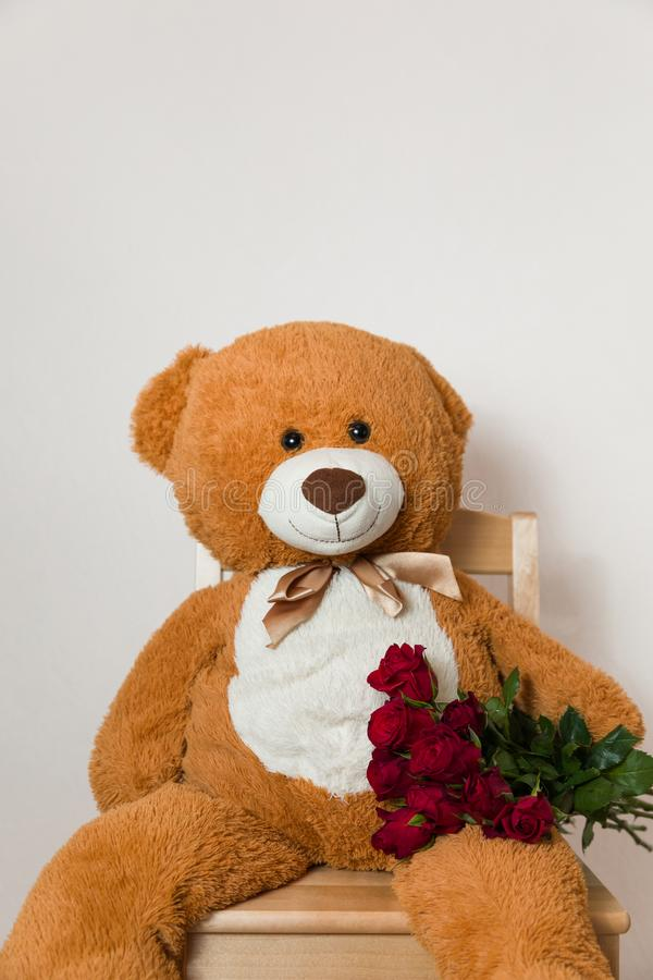 Big Teddy Bear holding red rose bouquet, romantic gift surprise, Valentines day, anniversary,love stock photo