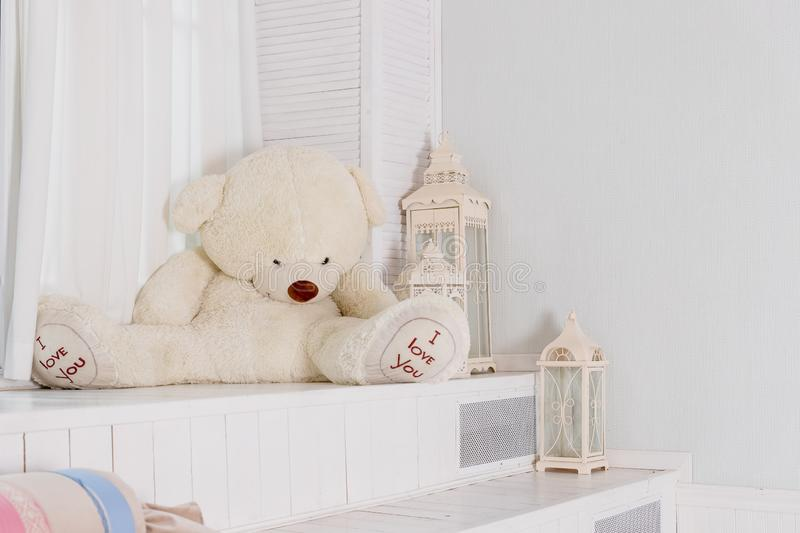 Big teddy bear near big white lantern,pillows in girly room. playroom interior.Beautiful child`s room in pastel tones royalty free stock photo