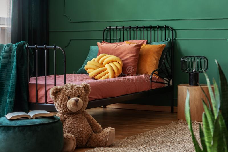 Big teddy bear and an open book on a green, velvet pouf in front of a metal frame bed in child`s bedroom interior. Real. Big, brown teddy bear and an open book stock image