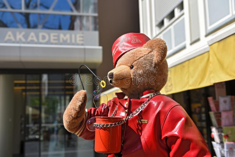 Big teddy bear with red hat and leather jacket blows soap bubbles in the air royalty free stock images