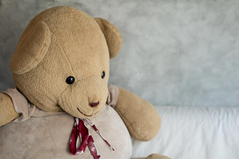 Big teddy bear on with sofa. In loft style room royalty free stock photo