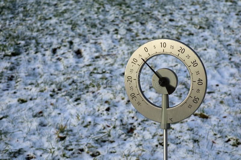 Big thermometer with celsius scale showing -5 degree placed in a frozen field with copy space royalty free stock photos