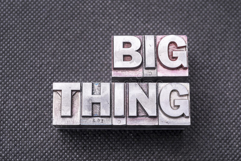 Big thing bm. Big thing phrase made from metallic letterpress blocks on black perforated surface royalty free stock photography