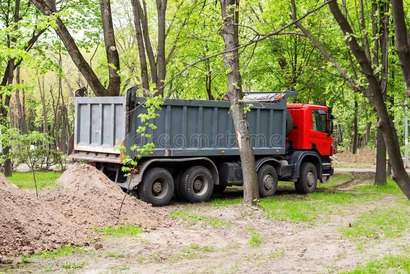 Big tipper truck near soil heap. Reconstruction of city park with heavy machinery royalty free stock photo