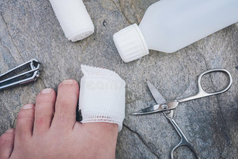 Big toe with band aid on. Grey background with nail clipper, scissors, band aid and desinfection bottle laying around. Healthcare, pain, medical and treatment stock photos