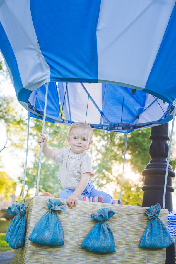 Big toy balloon in city park. Candy-table example. Birthday - one year old with figure number one. Baby boy seat inside royalty free stock images