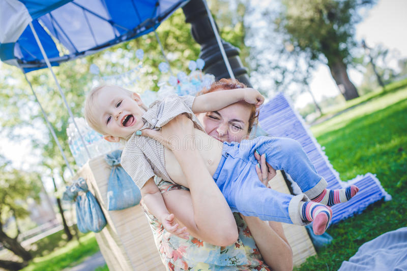 Big toy balloon in city park. Candy-table example. Birthday - one year old with figure number one. Mother and her son on grass. royalty free stock images