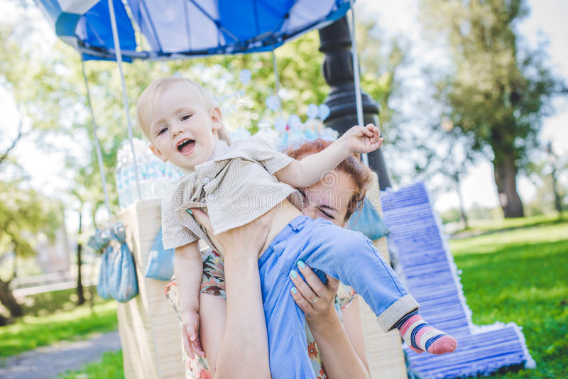 Big toy balloon in city park. Candy-table example. Birthday - one year old with figure number one. Mother and her son on grass. royalty free stock photo