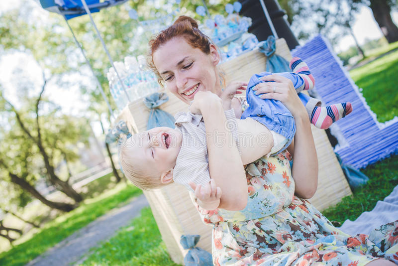Big toy balloon in city park. Candy-table example. Birthday - one year old with figure number one. Mother and her son on grass. royalty free stock image