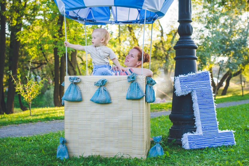 Big toy balloon in city park. Candy-table example. Birthday - one year old with figure number one. Mother and her son on grass. stock photography