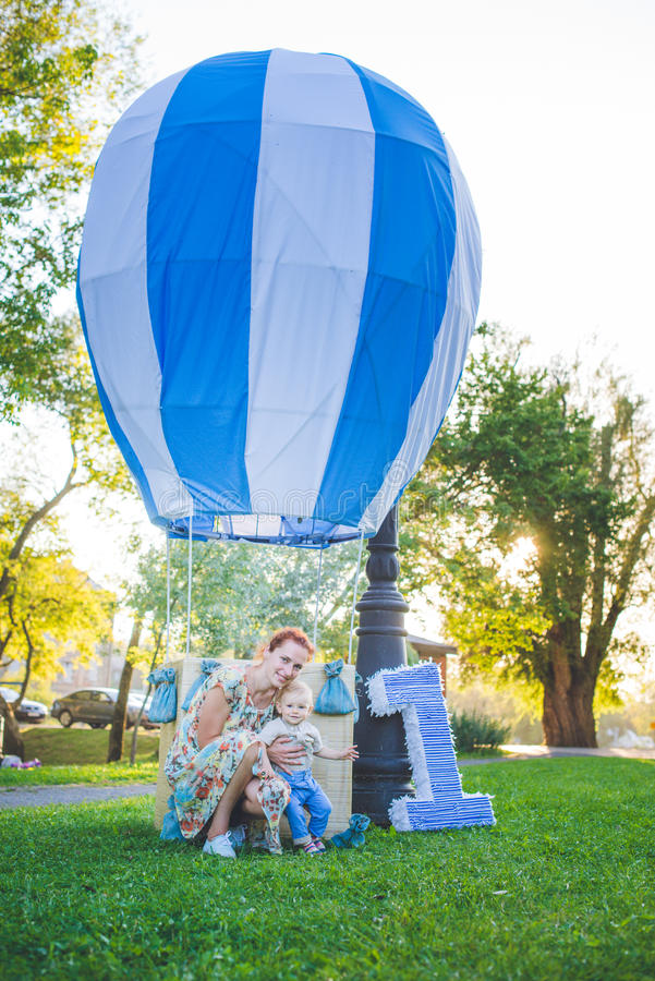 Big toy balloon in city park. Candy-table example. Birthday - one year old with figure number one. Mother and her son on grass. stock photos