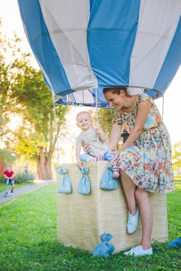 Big toy balloon in city park. Candy-table example. Birthday - one year old with figure number one. Mother and her son on grass. royalty free stock photography