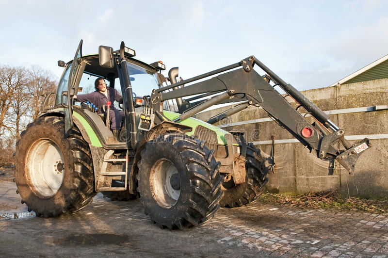 Big Tractor. Farm hand behind the wheel of a tractor, closing the door royalty free stock images