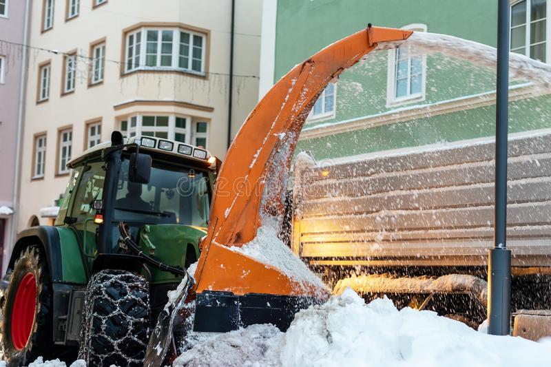 Big tractor with chains on wheel blowing snow from city street into dump truck body. Cleaning streets and snow removal after. Snowfall. Municipal services at royalty free stock image