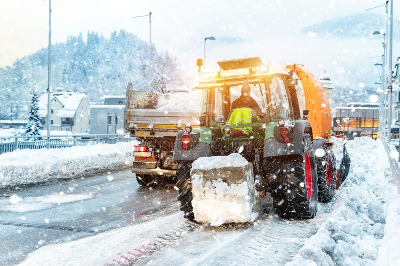 Big tractor with chains on wheel blowing snow from city street into dump truck body with snowblower. Cleaning streets royalty free stock photos