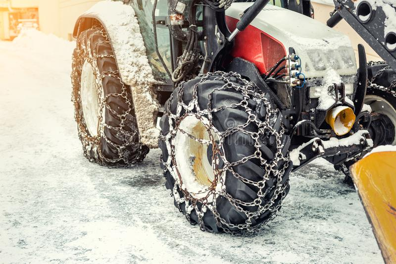 Big tractor machine with steel metal chains driving through slippery icy road or city street at alpine mountain region in winter royalty free stock image