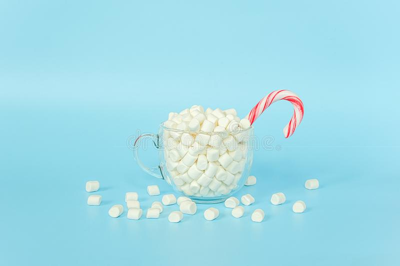Big transparent cup of marshmallows with red lollipop cane on blue background. Merry Christmas or Happy New Year concept. Minimal stock photo