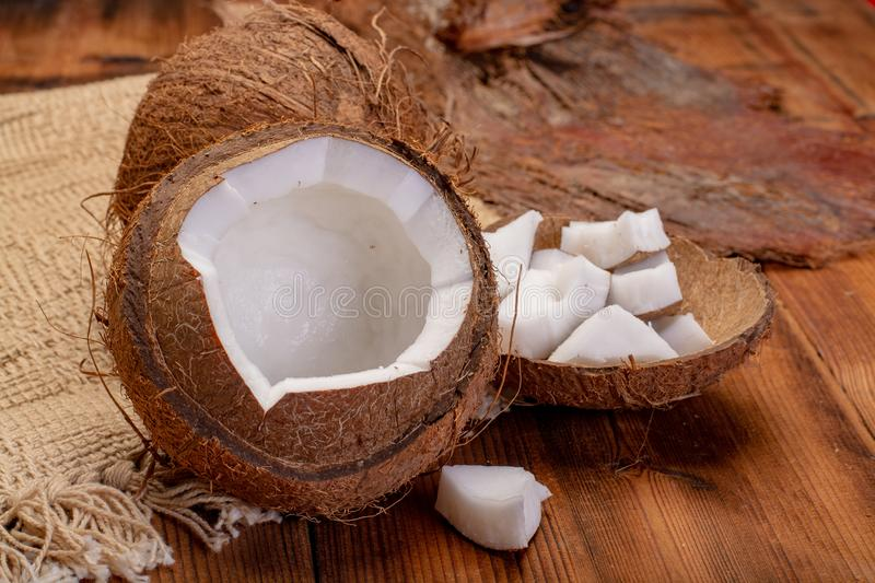 Big tropical palm nut coconut and coconut pieces ready to eat on. Wooden background close up stock image