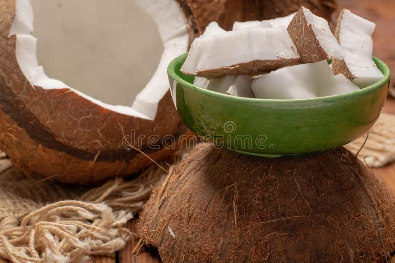 Big tropical palm nut coconut and coconut pieces ready to eat on. Wooden background close up royalty free stock photos