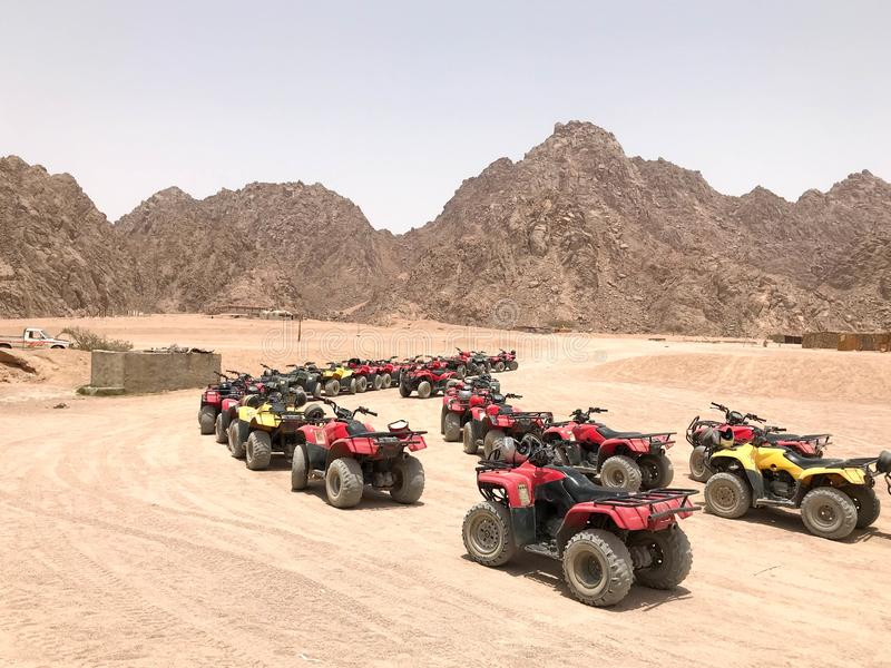 The big turn is a lot of four-wheeled multi-colored powerful fast off-road all-wheel drive ATVs, motorcycles in the sandy hot dese royalty free stock photography