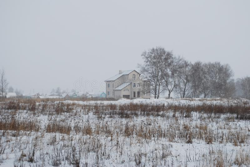 The big two-storeyed house stands in the middle of the snow-covered field. Snowfall. Russia stock photos