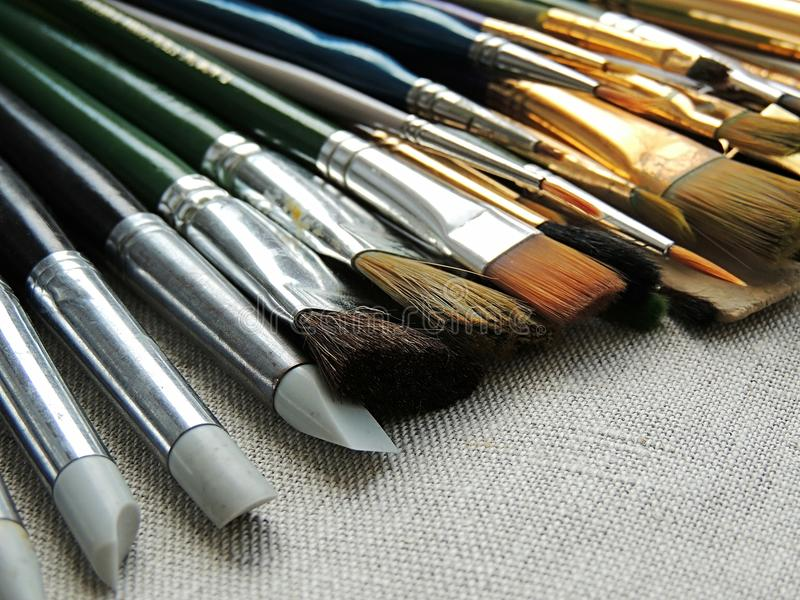 Big variety of brushes, tools for painting and sculpture on linen fabric background. stock photo