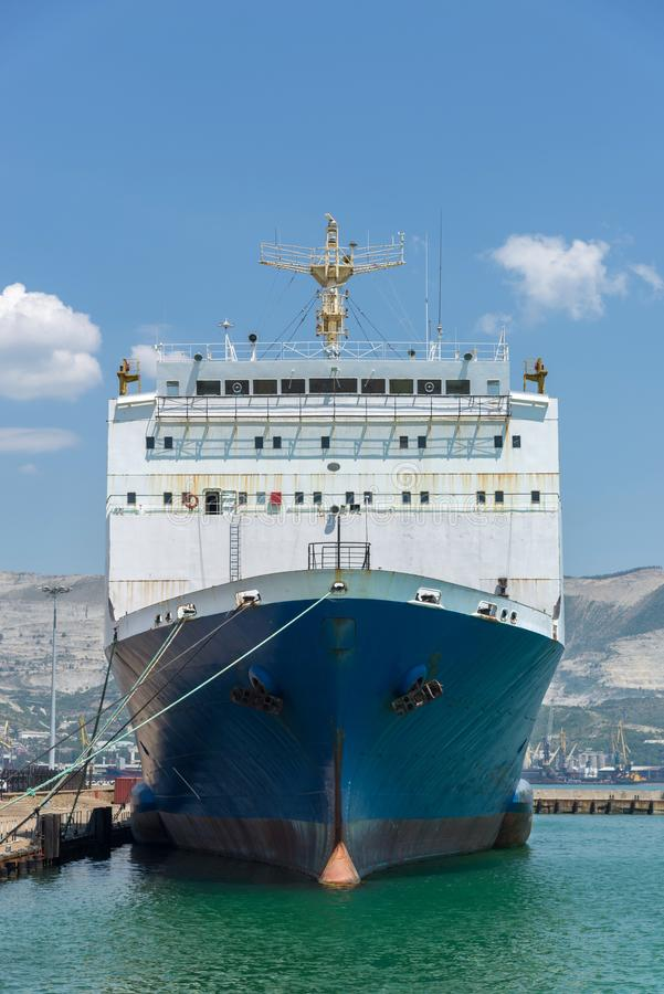 Vessel moorage on the berth. Big vessel moorage on the berth against the background of sky and mountains stock photo