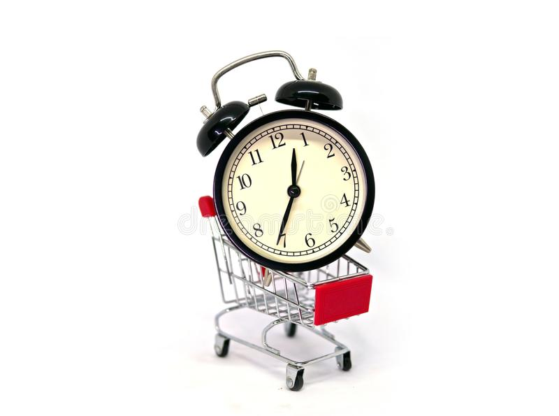 Big vintage alarm clock in a shopping cart or supermarket trolley isolated on white background. Buying time concept stock image