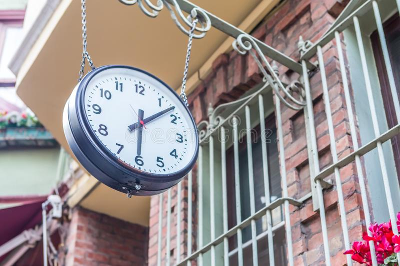 Big vintage old clock hanging with chain. On a stone window royalty free stock photo