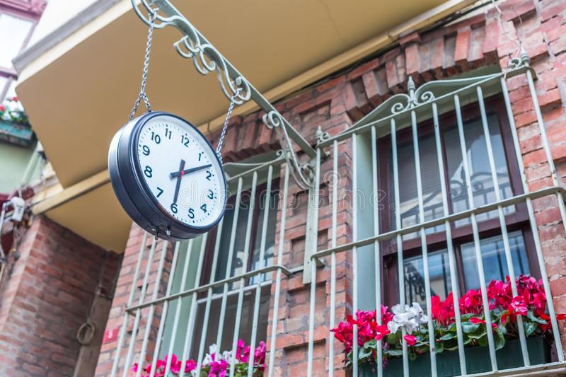 Big vintage old clock hanging with chain. On a stone window stock image