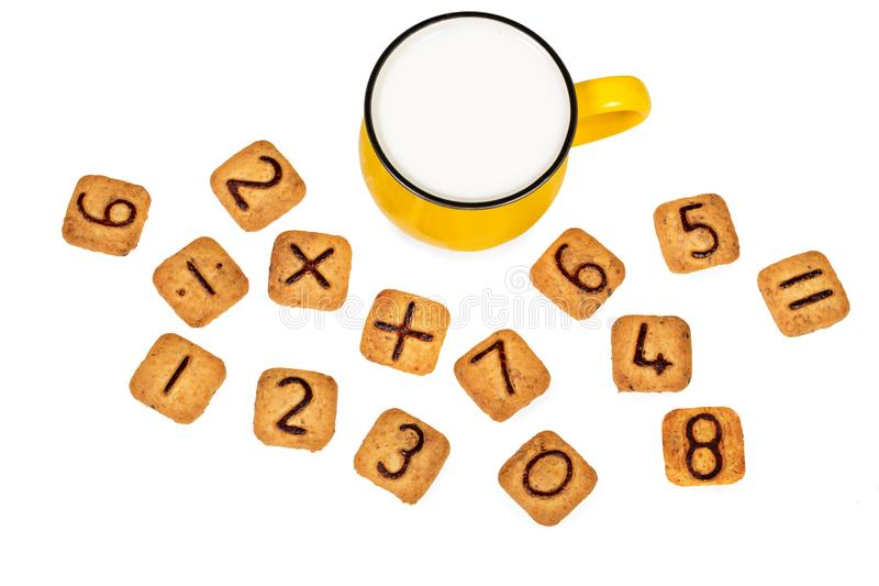 Big vivid yellow cup of milk and funny cookies with numbers isolated on white background. Healthy breakfast for a child. Idea of easy maths learning during royalty free stock photography