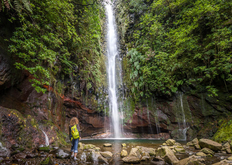 Big waterfall and woman hiker at levada 25 fountains in Rabacal, Madeira island. Woman tourist is standing next to the big waterfall at levada 25 fountains in stock photo