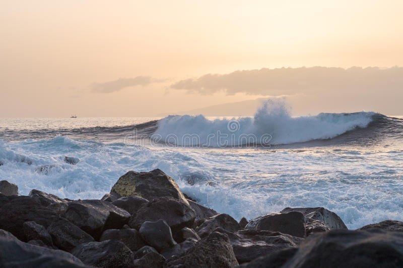 Big wave going to the rocky coast at sunset. Tenerife and La Gomera, Spain stock photography