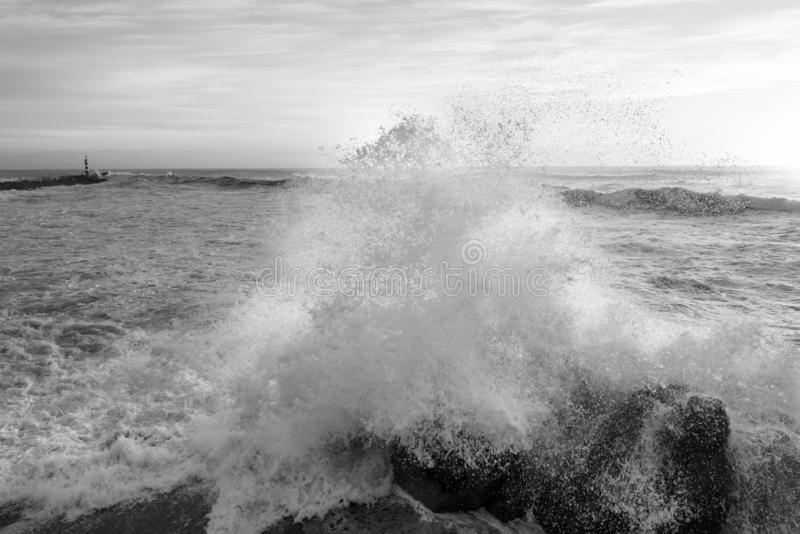 Big wave in Vila do Conde bay and lighthouse. Black and white seascape photography the bay of Vila do Conde ocean waves hit the rocks royalty free stock photography