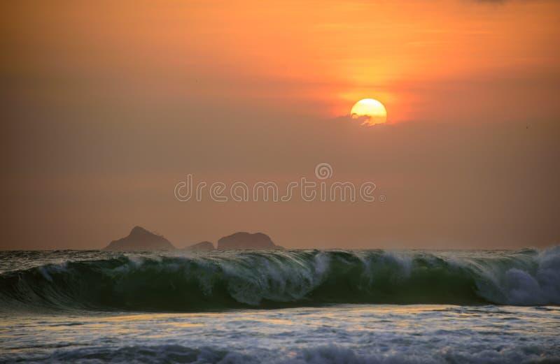 Big waves of Atlantic ocean at Ipanema beach and beautiful sunset with clouds and orange sky, Rio de Janeiro stock photo
