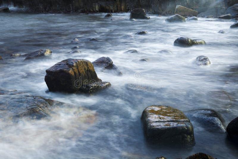 Big waves crash on rocky beach stock images