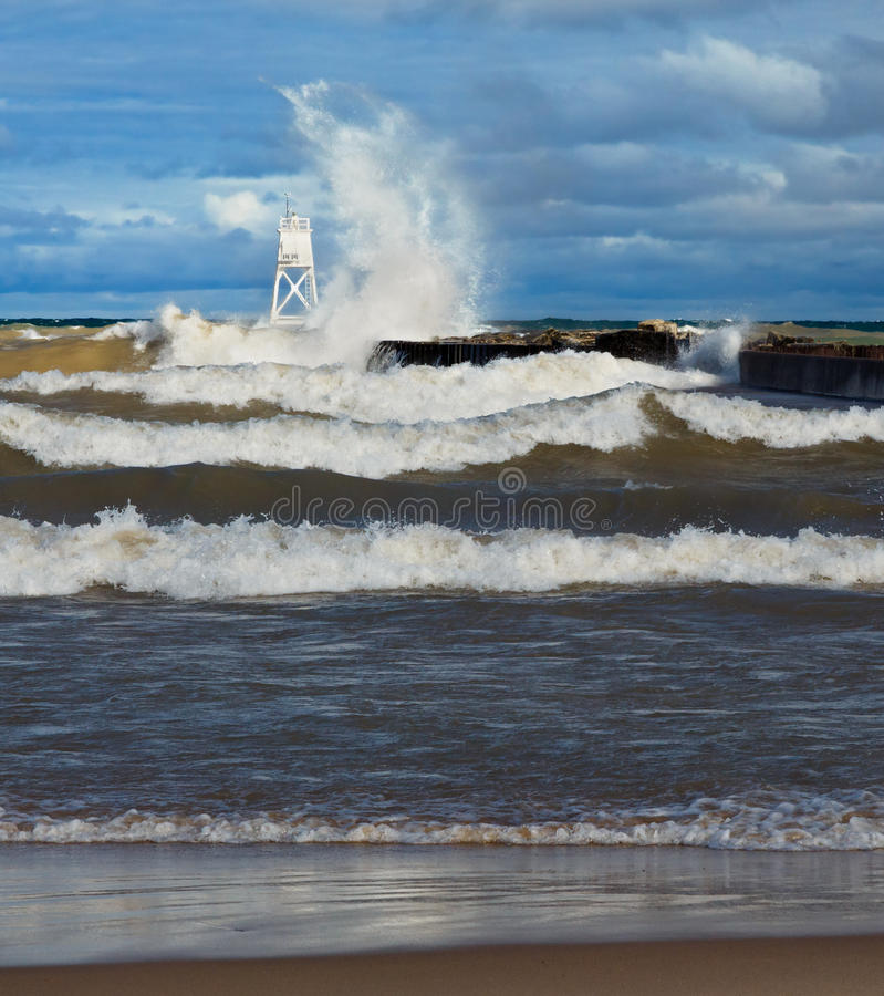 Big Waves at Grand Marais. Lake Superior waves crash into the pier of the Outer Range Lighthouse at Grand Marais in Michigan's Upper Peninsula royalty free stock photo