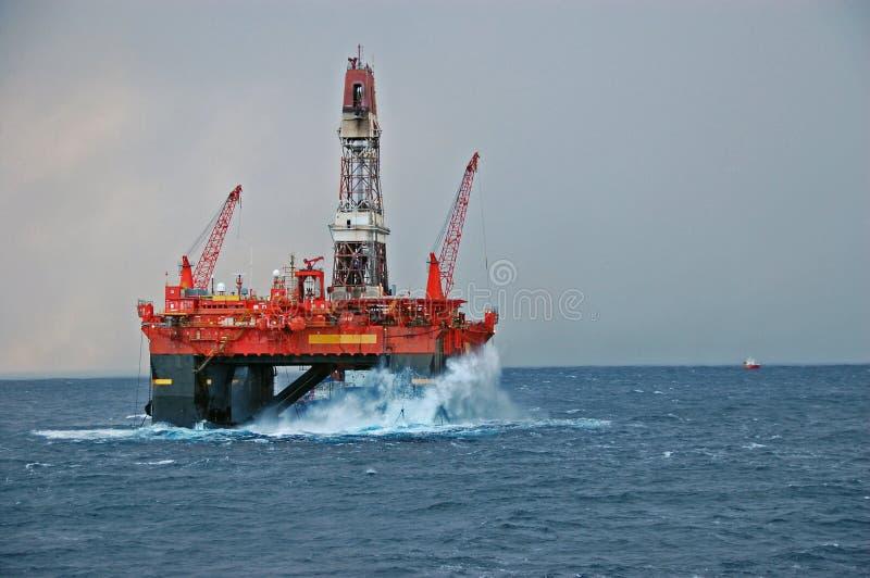 Big waves hitting a Semi submersible drilling rig stock image