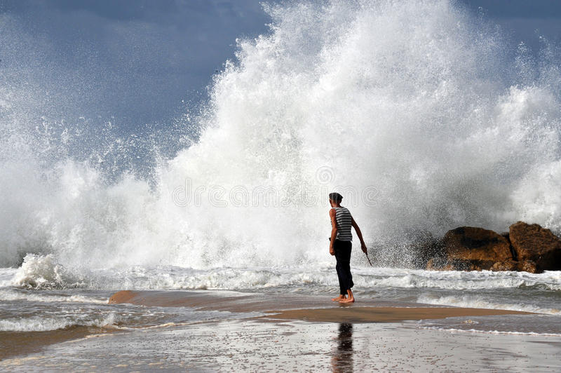 Big waves in Israel. ASHKELON - NOV 02:Israeli man walk into a giant wave on Nov 02 2009.According to a recent research about consequences of rising sea levels stock photos