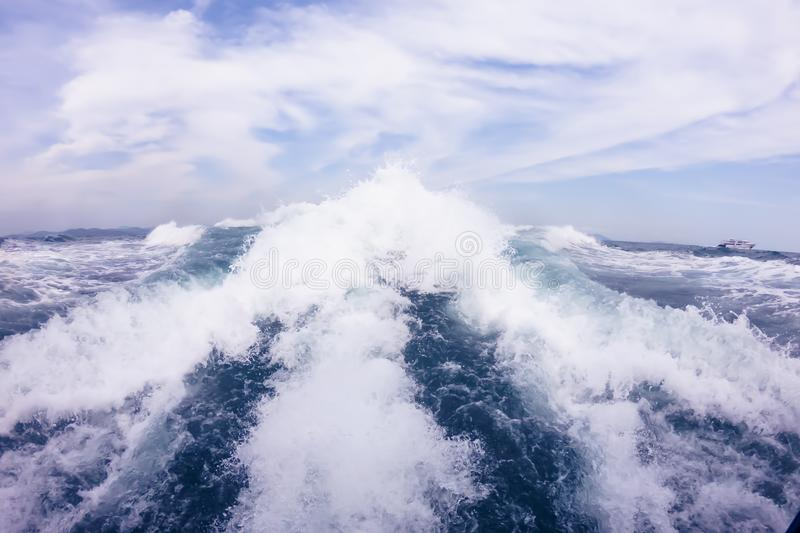 Big waves from the motor behind the speedboat on the high seas. Blue sky with white clouds.  royalty free stock images