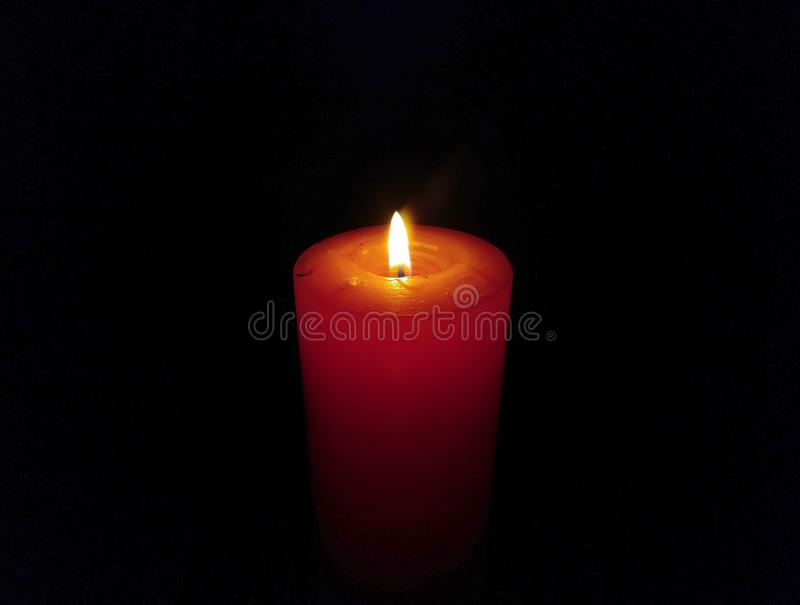A Big Wax Candle Burning Isolated on Black Background royalty free stock photo