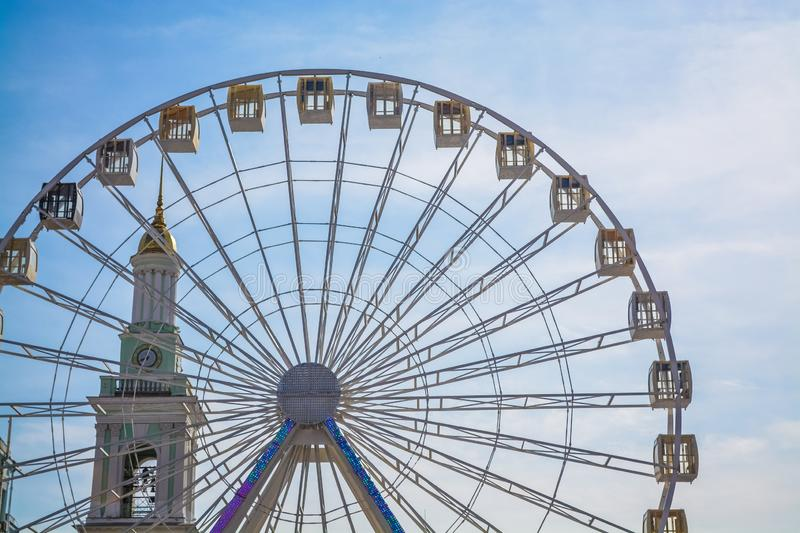 Big wheel against the background of the blue sky and an old city architecture Kiev, Ukraine. Amusement park. Area. royalty free stock photos