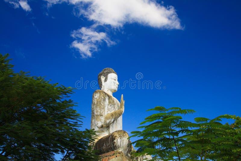 Big white Buddha statue raising high contrasting with blue cloudless sky at Wat Ek Phnom, near Battambang, Cambodia. Big white Buddha statue raising high stock photos